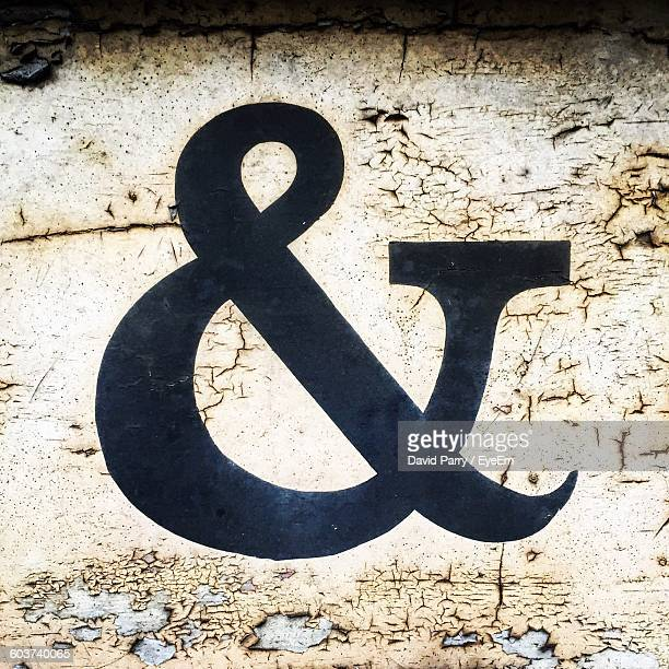 Close-Up Of Black Ampersand Sign On Weathered Wall