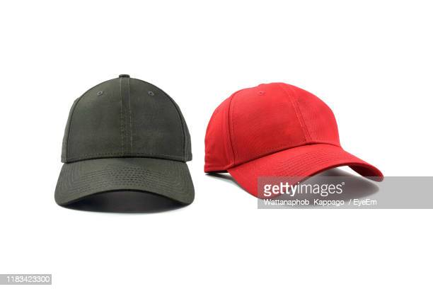 close-up of black and red cap against white background - hat stock pictures, royalty-free photos & images