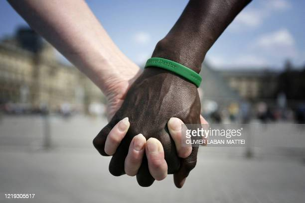 Close-up of black and white people joining their hands in the human chain organized 28 April 2007 in front of the Louvre Museum in Paris between the...