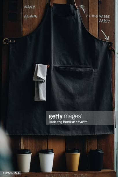 close-up of black apron and disposable glass against wooden wall - schürze stock-fotos und bilder
