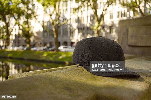 close-up of black baseball cap on retaining wall - bones - fotografias e filmes do acervo