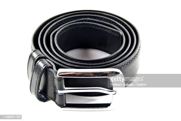 close-up of black belt against white background - black belt fashion item stock pictures, royalty-free photos & images