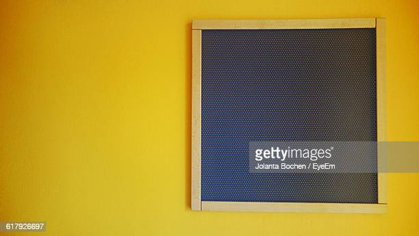 Close-Up Of Black Board On Yellow Wall