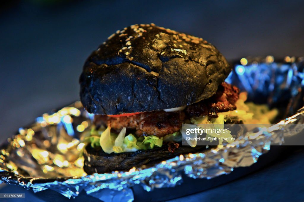 Close-Up Of Black Bun Burger On Foil In Plate : Stock Photo