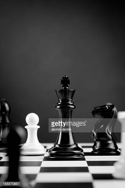 Close-up of Black Chess King among other figures on chessboard