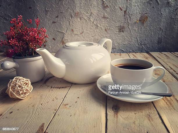 Close-Up Of Black Coffee By Teapot And Flower Vase On Table
