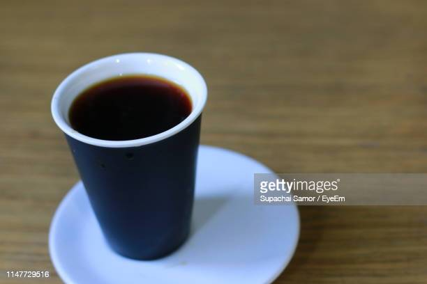 close-up of black coffee on wooden table - eye black stock photos and pictures
