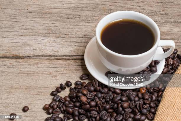 close-up of black coffee with roasted beans on table - black coffee stock pictures, royalty-free photos & images