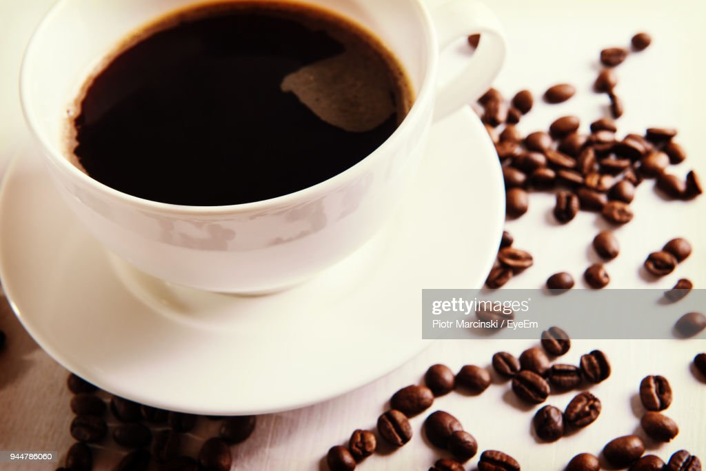 Close-Up Of Black Coffee With Roasted Coffee Beans On Table : Stock Photo