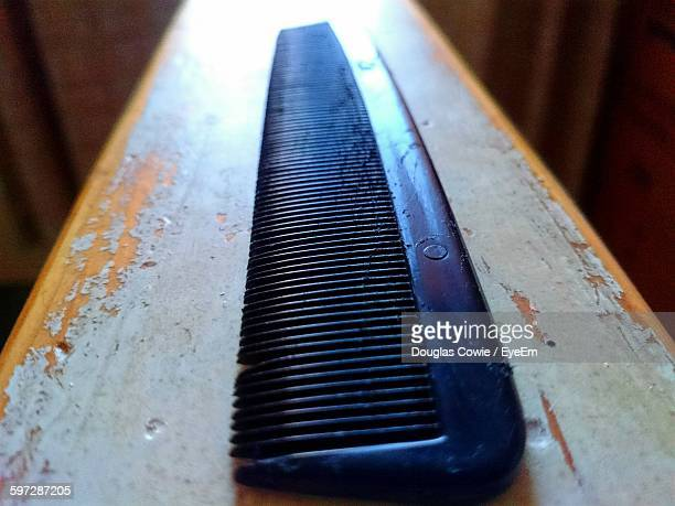 Close-Up Of Black Comb On Wooden Table