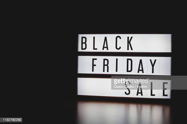 close-up of black friday sale text on information sign against black background - black friday stock photos and pictures