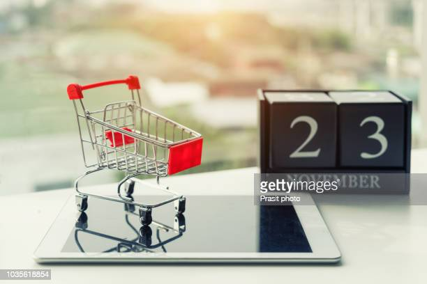 close-up of black friday super sale banner on digital tablet with shopping cart. - black friday stock photos and pictures