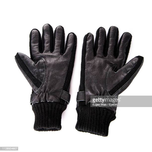 close-up of black gloves over white background - leather glove stock pictures, royalty-free photos & images