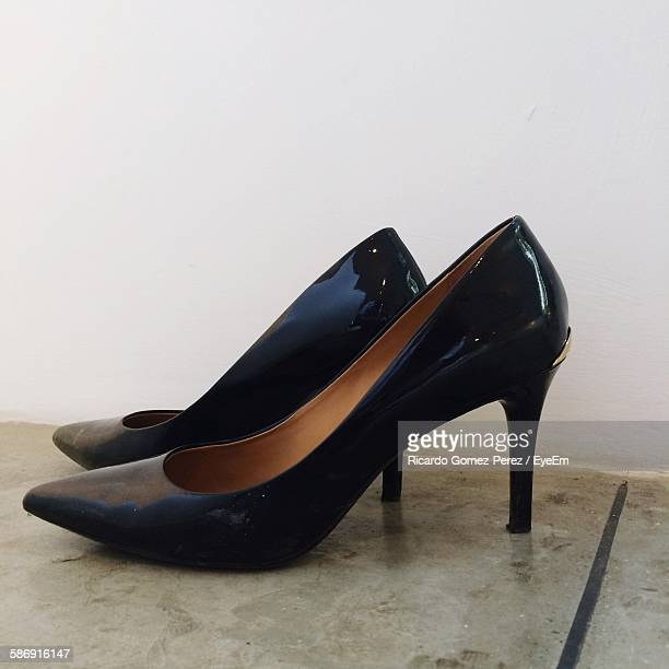 Close-Up Of Black High Heels On Floor Against White Wall