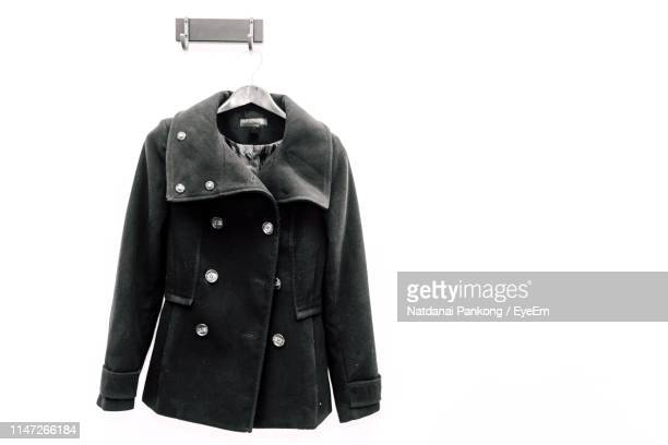 close-up of black jacket hanging from hook over white background - black coat stock photos and pictures