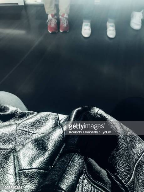 Close-Up Of Black Leather Jacket With People Standing On Floor In Background