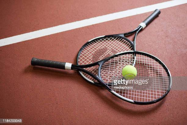 primo piano di racchette moderne nere con palla verde chiaro sdraiata sul pavimento del campo da tennis, sport e concetto di hobby - tennis foto e immagini stock