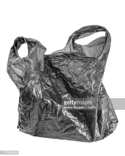 close-up of black plastic bag against white background - plastic bag stock pictures, royalty-free photos & images