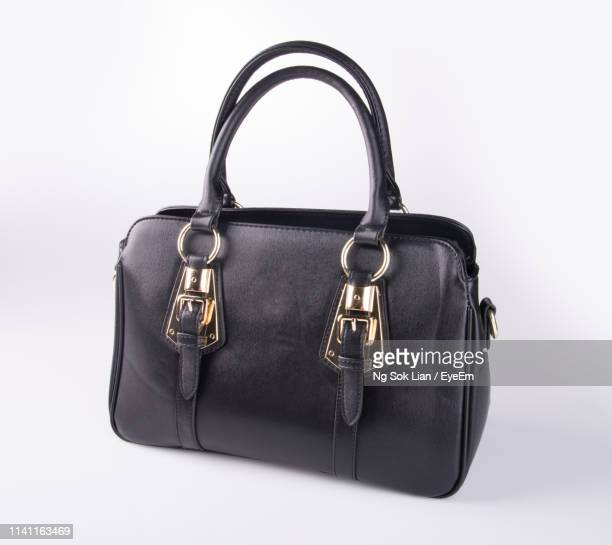 close-up of black purse against white background - handbag stock pictures, royalty-free photos & images