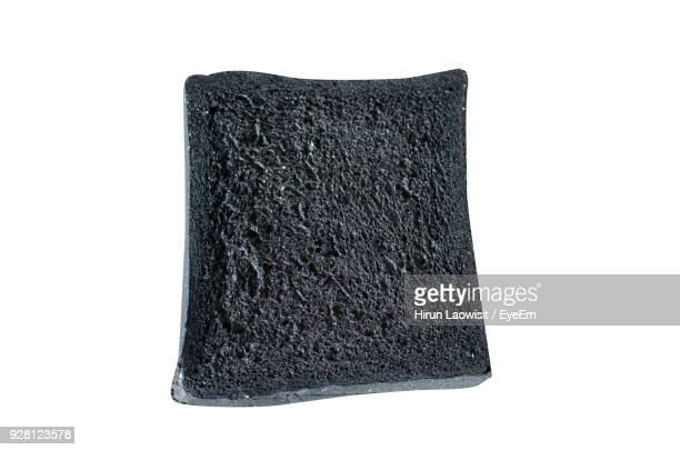 Close-Up Of Black Rye Bread Against White Background