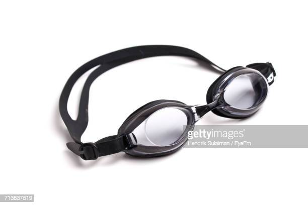 close-up of black swimming goggles against white background - zwembril stockfoto's en -beelden