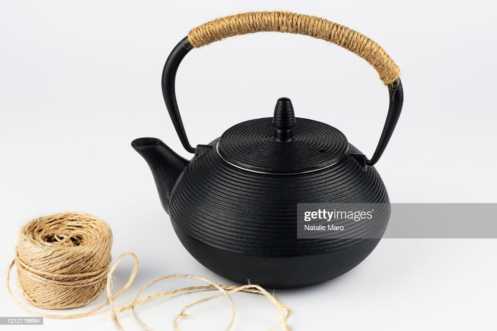 Closeup of black teapot with rope on handle and a skein of rope on white background : Stock Photo