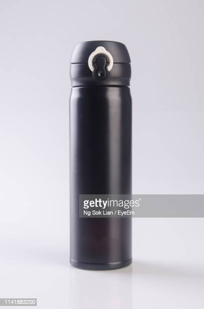 close-up of black water bottle against white background - cylinder stock pictures, royalty-free photos & images