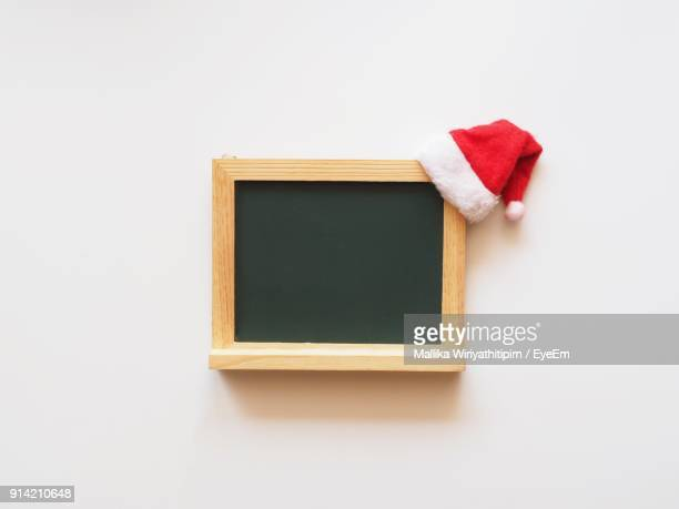 Close-Up Of Blackboard And Santa Hat Over White Background