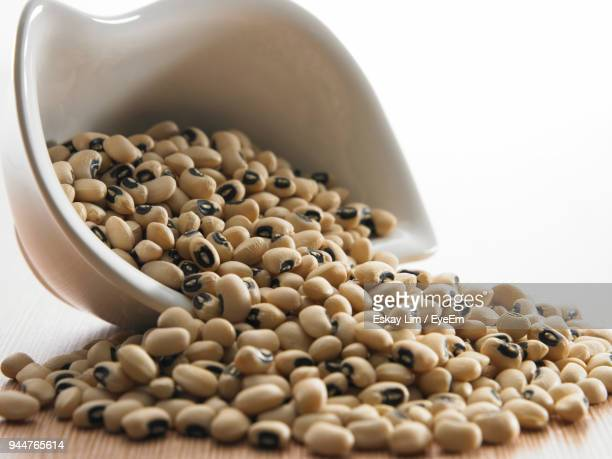 close-up of black-eyed peas in bowl on table against white background - black eyed peas food stock pictures, royalty-free photos & images