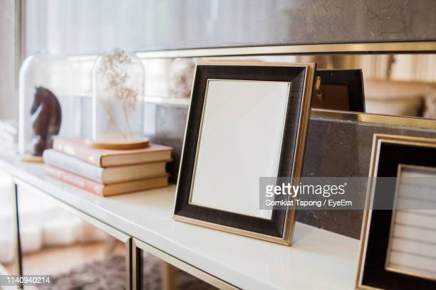 close-up of blank frame on shelf at home - photo frame stock pictures, royalty-free photos & images