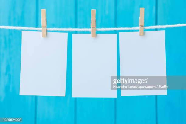 Close-Up Of Blank Notes Hanging Clothesline Against Blue Wall