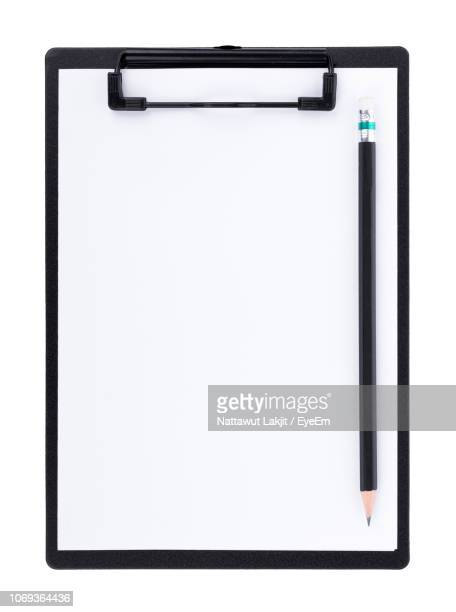 close-up of blank paper in clipboard with pencil against white background - klemmbrett stock-fotos und bilder