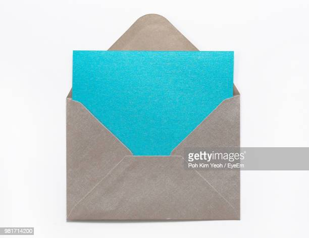 close-up of blank paper with envelope against white background - envelope stock pictures, royalty-free photos & images