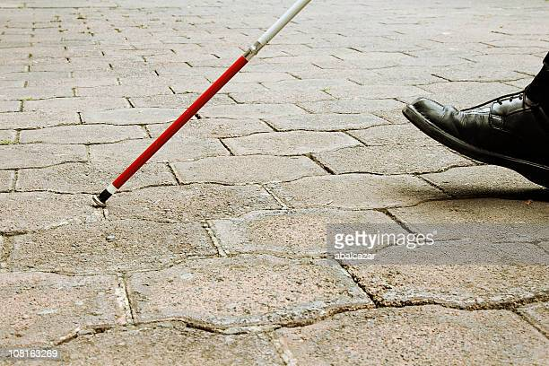 closeup of blind man walking with white cane - walking cane stock photos and pictures