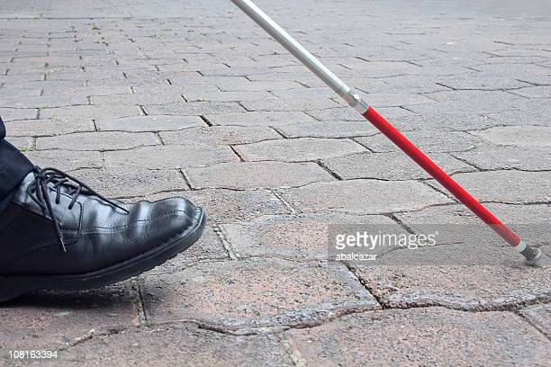 close-up of blind man's black shoe and white cane walking - walking cane stock photos and pictures