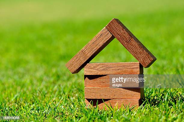 Close-up of blocks of wood forming a small house on grass
