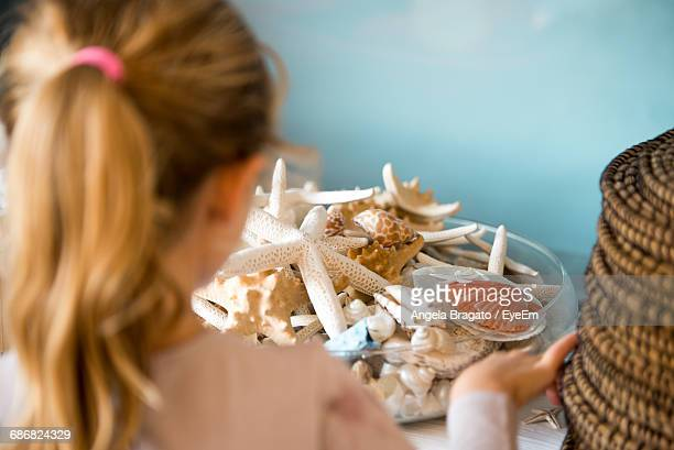 Close-Up Of Blonde Girl With Seashells In Home