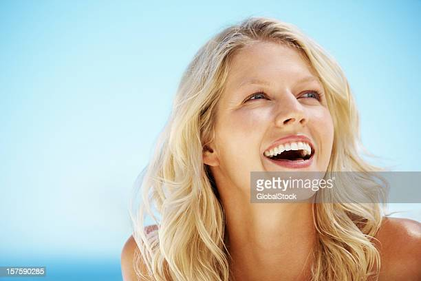 Close-up of blonde woman looking at blue sky
