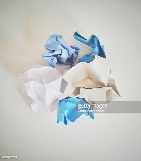 Close-Up Of Blue And White Crumpled Papers On Table