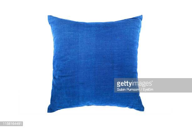 close-up of blue cushion against white background - cushion stock pictures, royalty-free photos & images