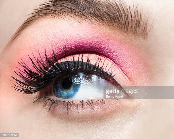 Close-up of blue eye with pink eye shadow