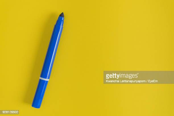 close-up of blue felt tip pen on yellow background - felt tip pen stock pictures, royalty-free photos & images
