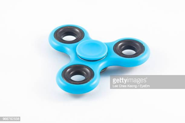 Close-Up Of Blue Fidget Spinner Over White Background