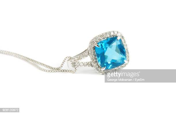 Close-Up Of Blue Gemstone Pendant With Chain Against White Background
