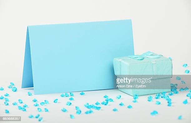 Close-Up Of Blue Greeting Card And Gift Box With Rhinestones On White Background
