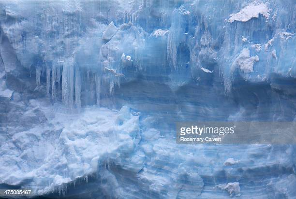 Close-up of blue ice and icicles on iceberg