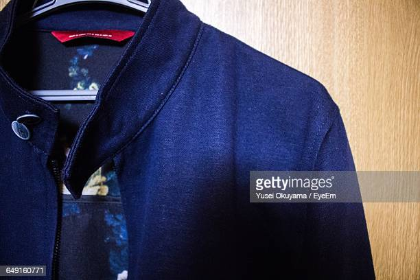 close-up of blue jacket hanging on wardrobe - blue jacket stock pictures, royalty-free photos & images