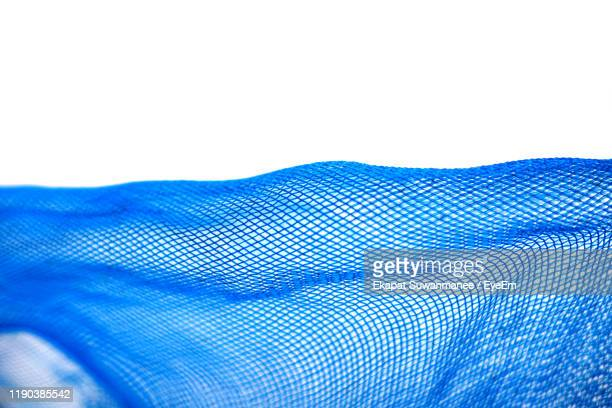 close-up of blue net against white background - 網状 ストックフォトと画像