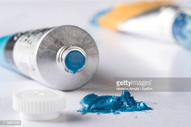 Close-Up Of Blue Paint By Tube On Table