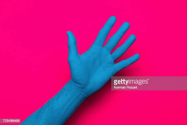 close-up of blue painted hand against pink background - palma da mão imagens e fotografias de stock